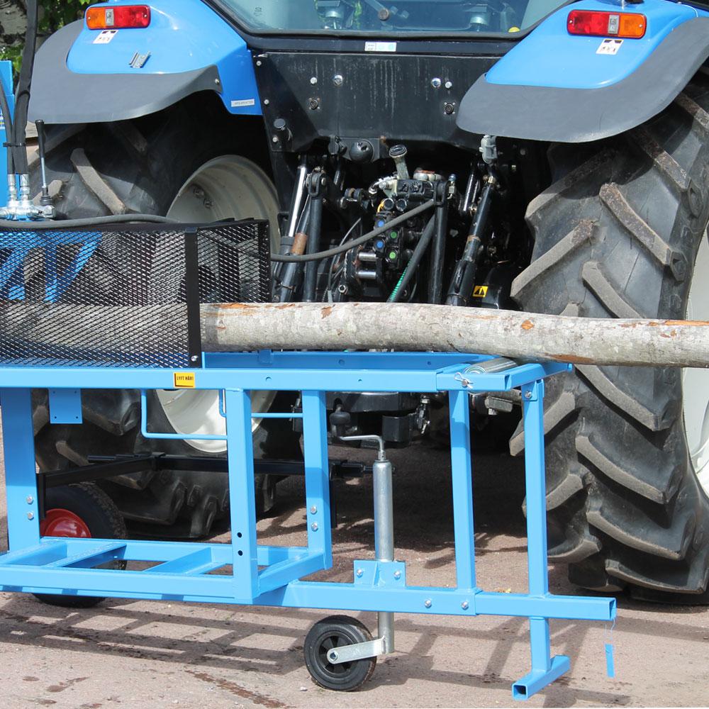 Vedmaskin traktordrift framför en traktor