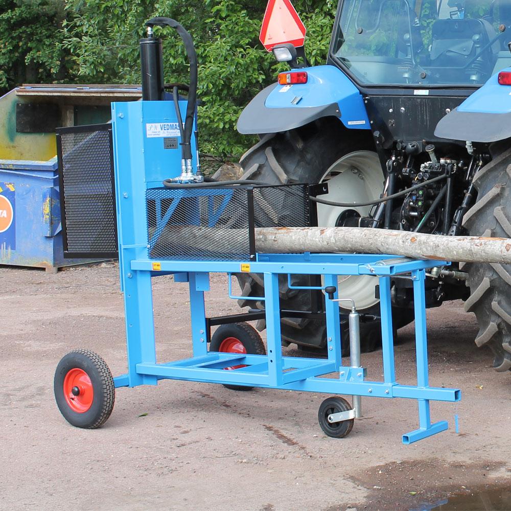 Vedmaskin traktordrift kopplad till en traktor